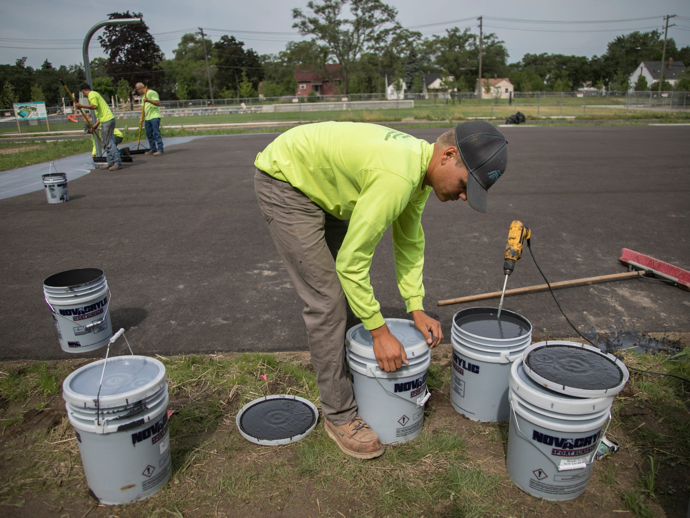Michigan Recreational Construction employee Tye Pennala, 19, of Howell, prepares paint for a new basketball court in the Fitzgerald neighborhood on June 25 in Detroit.