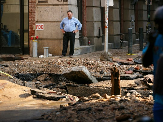A man stands near a water main break that occurred
