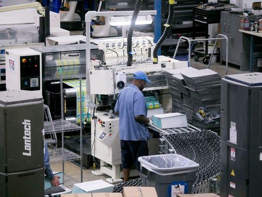 A worker works on a fan folder machine at Pollard Banknote
