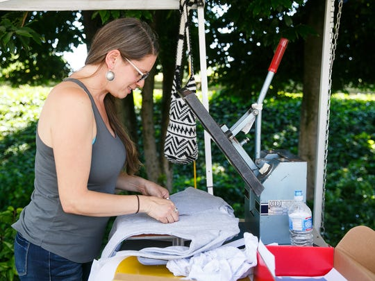 Roanna Gingrich with Rofe Designs presses a t-shirt at the West Salem Farmer's Market on Thursday, July 5, 2018. Gingrich set up a 'design your own shirt' booth as part of her regular hand-drawn apparel business.