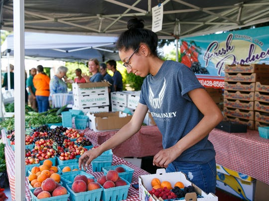 Jazlyn Munoz packs up a box of fruit for a customer at Pablo Munoz Farms at the West Salem Farmer's Market on Thursday, July 5, 2018. This is the first week the market, located along Edgewater Street NW, is open.