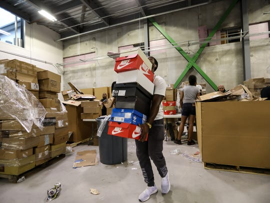 Tre Cadwell, 22, of Farmington carries sneakers to