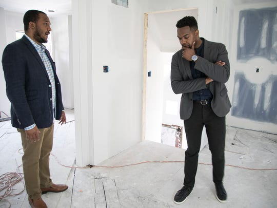Century Partners cofounders Andrew Colom, left, and David Alade, check out one of the homes under construction in the Fitzgerald neighborhood on Lilac Monday, June, 25, 2018 in Detroit. The house on Lilac will be the first home fully rehabbed as part of the Fitzgerald revitalization project. Century Partners is supposed to rehab about 100 homes in the neighborhood by winter 2020.