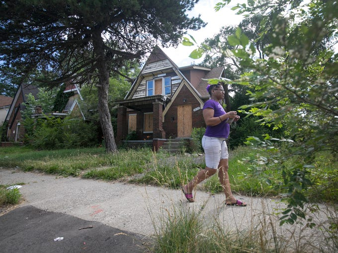 A woman walks by this blighted house on Woodingham,