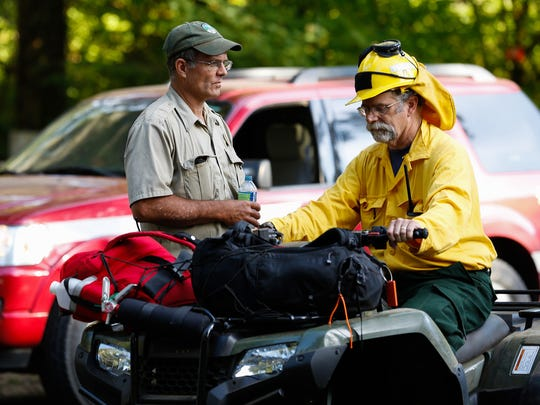 Two men talk during the evacuation of Camp Silver Creek in Silver Falls State Park on Friday, July 13, 2018.