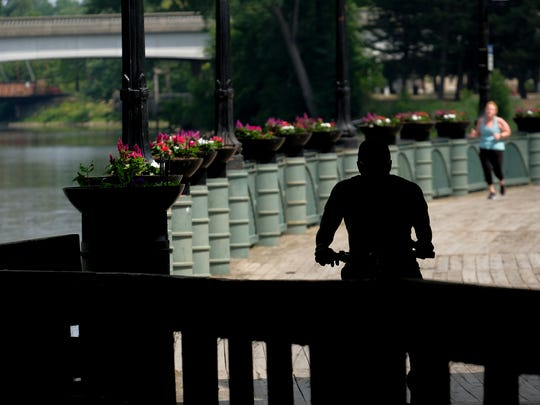 Bicyclists and joggers use the boardwalk along the rivertrail Sunday, July 15, 2018.