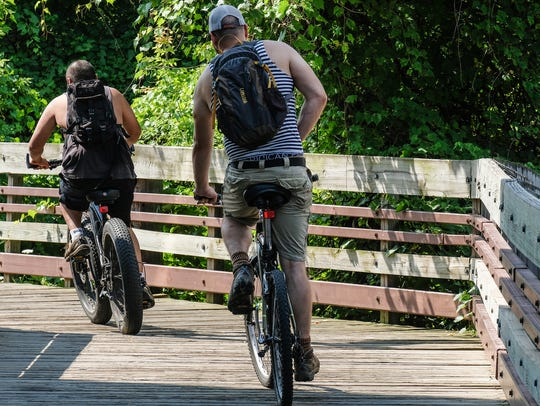 A pair of bicyclists use the rivertrail Sunday, July