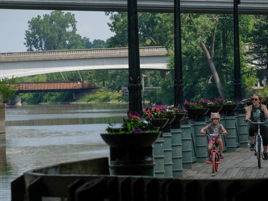 Families use the riverwalk for rides through downtown Lansing Sunday, July 15, 2018.