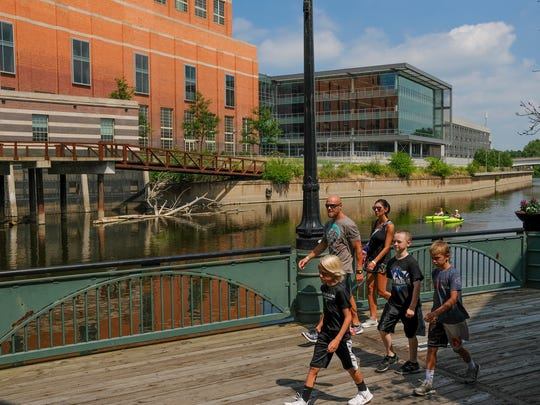 Families walk and kayakers paddle the Grand River in downtown Lansing Sunday, July 15, 2018.