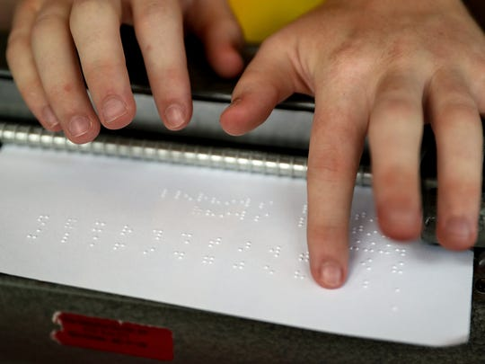 Mitchell Bridwell reads letters that he typed on his Perkins Brailler typing machine, which is used in competition for the Braille Challenge, at his family's home in Pittsboro, Ind., Thursday, July 12, 2018. The 17-year-old recently won the Braille Challenge varsity championship for the second consecutive year at the University of Southern California. Bridwell will be a senior at the Indiana School for the Blind and Visually Impaired this fall.