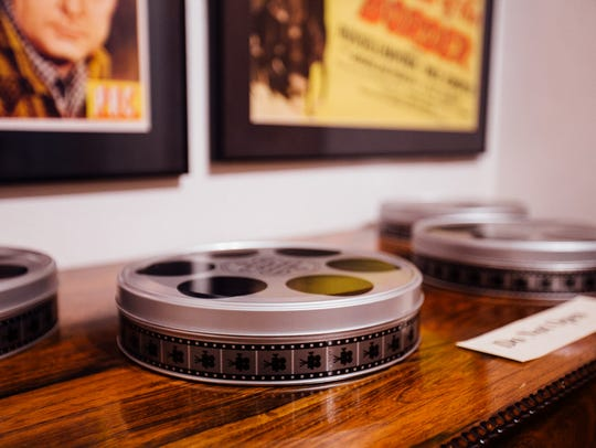 Film reel canisters sit on a shelf in the basement