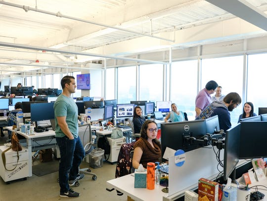 Employees work at their desks in the HelloWorld, Inc.