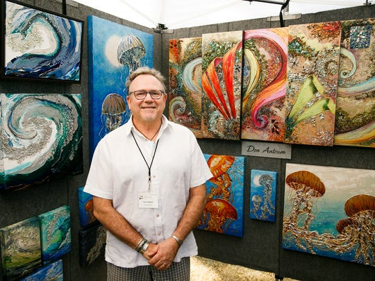 Don Antram of Roseville, Cali., stands with his mixed-media art work at the Salem Art Fair on Friday, July 20, 2018, in Bush's Pasture Park. Antram's art incorporates molding pasta and glass pieces to create textured paintings with an ocean theme.