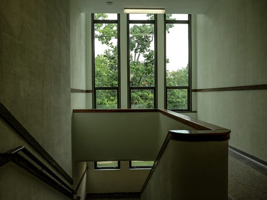 A stairwell has the light of tall window at the new