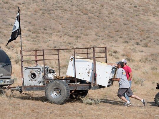 Dayton Pigs volunteers load an illegally dumped refrigerator