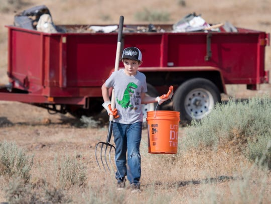 JJ Lucas, 8, heads out to pick up more garbage after