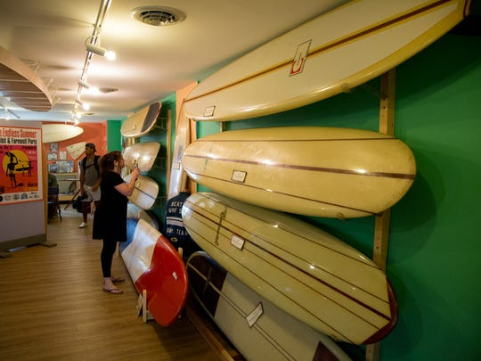 Journalist Tara Nurin examines the antique surf boards at the Surf Museum in Tuckerton seaport.