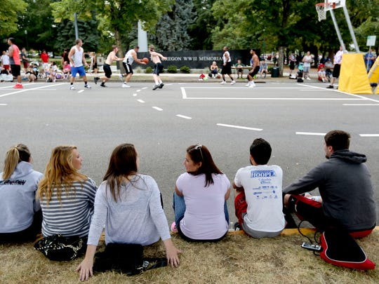 Fans watch a game during the Hoopla basketball tournament outside the Oregon State Capitol in Salem on Sunday, Aug. 7, 2016.
