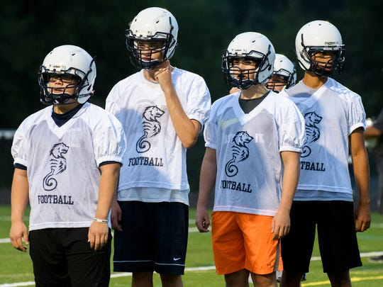 The players listen to the coach give stretching instructions during the first practice of the season for the South Burlington/Burlington SeaWolves at South Burlington High School on Monday evening August 13, 2018 in South Burlington.