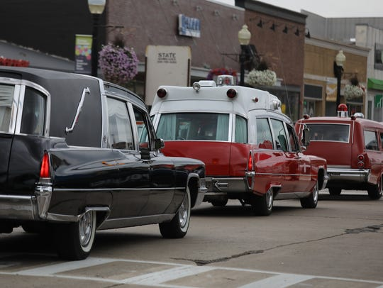 Hearses, ambulances, and flower cars line up for the
