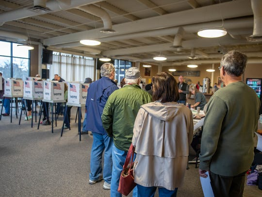 Voters line up to casts their ballots on Tuesday at