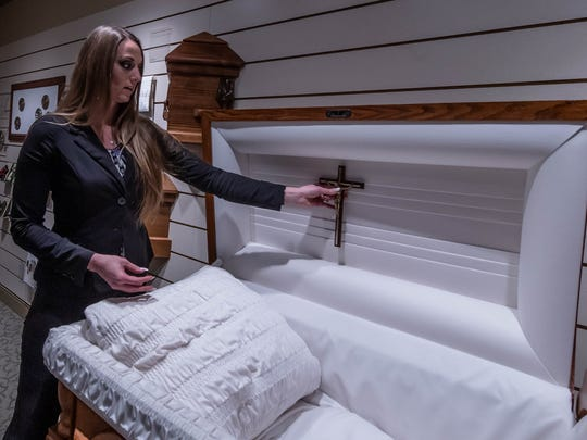 Funeral Director Jenelle Vandegriff shows one of many optional elements that goes into the lid of a cremation casket at Kempf Family Funeral and Cremation Services in Battle Creek.