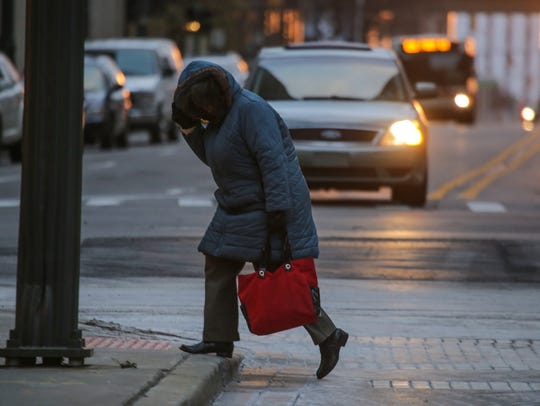 A woman shields herself from the cold wind while crossing