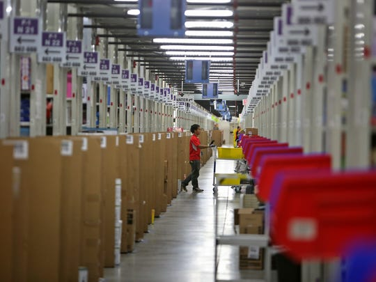 A worker fills orders in the huge picking area at the Amazon Whitestown fulfillment center in a December 2014 file photo.