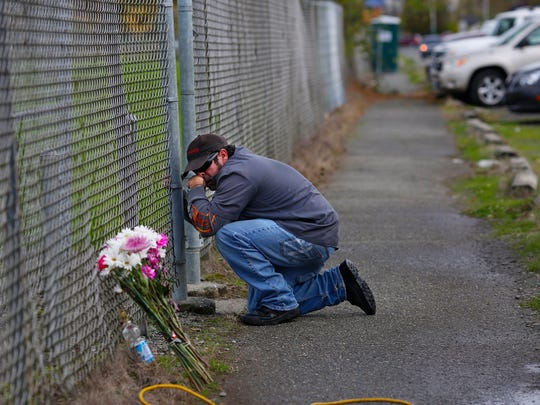 Dale Zachry, who graduated from Marysville-Pilchuck High School in 1986, stopped for a prayer at the fence surrounding the school grounds in Marysville, Wash., Saturday, Oct. 25, 2014.