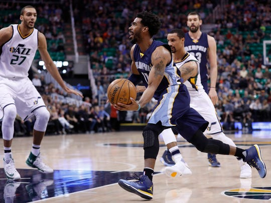 Memphis Grizzlies guard Mike Conley (11) drives to the hoop against Utah Jazz guard George Hill (3) and center Rudy Gobert (27) in the first quarter at Vivint Smart Home Arena.