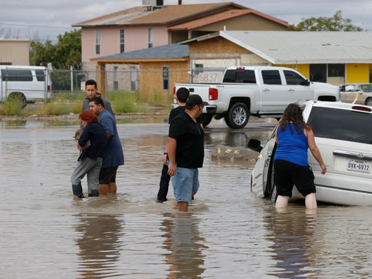Residents help an unidentified woman to dry ground Thursday morning after she drove her van into a small canal along West Street in the parking lot of the Family Dollar store in Canutillo. Doniphan Drive and many other smaller streets in Canutillo were impassable for residents and business owners after the heavy rains flooded many parts of Canutillo.
