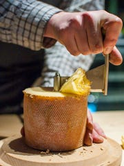 Rory Stamp, artisan food manager at the Dedalus Wine Shop in Burlington, uses a girolle to shave a round of Tete de Moine cheese on Friday, February 17, 2017. The girolle is specially made for use with this cheese from Switzerland.