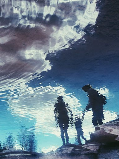 family's reflection in water