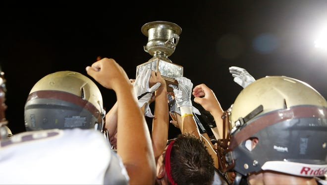 Clarkstown South hoist the supervisors trophy after defeating Clarkstown North 14-13 at Clarkstown North High School in New City on Friday, September 02, 2016.  Clarkstown South won 14-13.