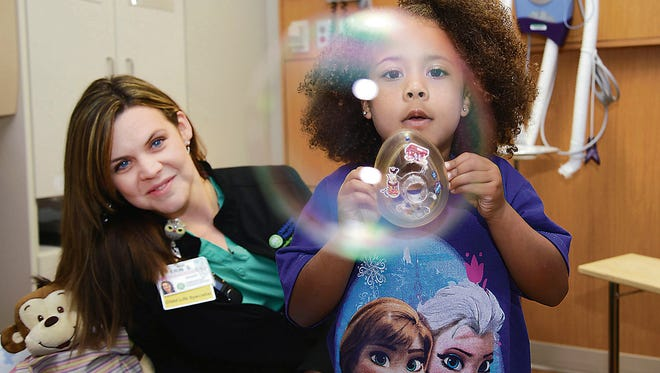 Erin Shaffer, a Child Life Specialist at the Children's Hospital at Greenville Health System, uses bubbles to show a child how to breathe through an oxygen mask.