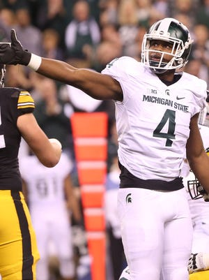 Michigan State Spartans defensive lineman Malik McDowell (4) signals possession during the Spartans' Big Ten championship win over Iowa.