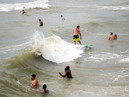 Beachgoers and surfers ride the waves by Naples Pier