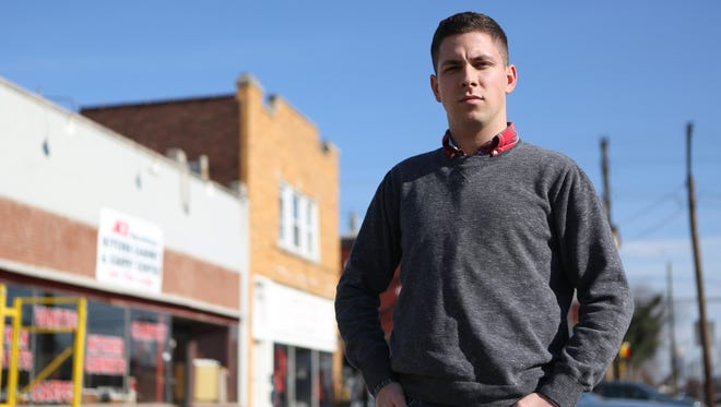 """Jeff Holiday, a young filmmaker at Ball State University whose home is in Georgetown, Ind., is seen in front of the former Newkirk Drugs store in Portland. His grandfather Dual """"Wayne"""" Hinton, 67, and his wife, Shelby Hinton, 65, had owned the drugstore for more than 30 years before their deaths in 2005 — after Wayne Hinton shot his wife at their Georgetown, Ind. home and then shot himself. Holiday and a team are making a film about the stigma surrounding suicide and mental illness called """"Boulevard"""" and are raising money at Indiegogo.com."""