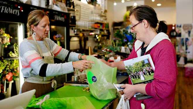 Owner Marcy Almoney, left, of  Foster's Flower Shop, answers questions and sends bride-to-be Amy Elizabeth Burger, of York City, home with some magazines to help her get an idea of what she might like for her wedding during Burger's first visit to the store in York City, Tuesday, May 2, 2017. Dawn J. Sagert photo