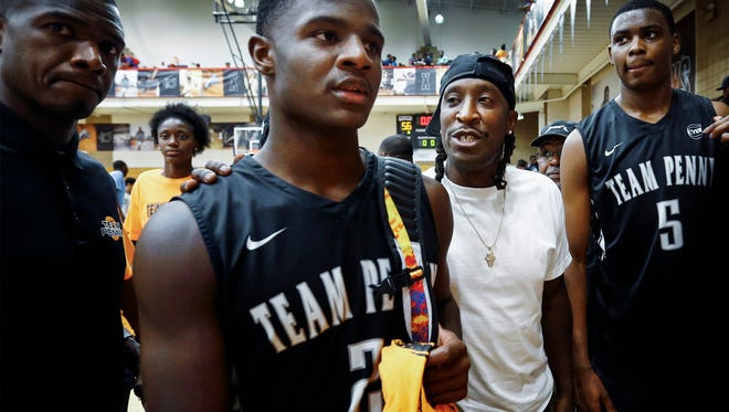 Team Penny point guard Alex Lomax, Jr. is consoled by father Alex Lomax, Sr. (middle right) after losing to Boo Williams 63-56 at the 2017 Nike Peach Jam in North Augusta, S.C., in July 2017.