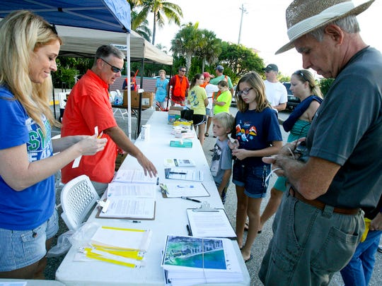 City of Bonita Springs spokeswoman Lora Taylor and City Manager Carl Schwing help get volunteers signed in during the annual Beach Cleanup, organized by the city in 2013.