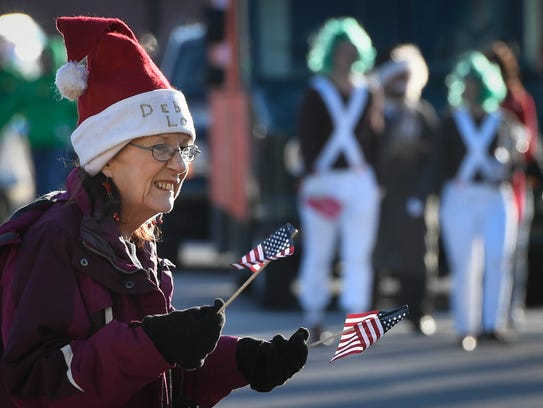 Parade lover Debbie Lou Heiken waves dueling flags