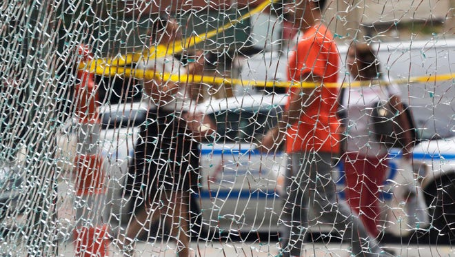 New Yorkers pass a shattered storefront window on W. 23rd St. in Manhattan, Tuesday, Sept. 20, 2016, in New York. The window was hit by shrapnel from the terrorist bomb that exploded across the street Saturday evening. An Afghan immigrant wanted in the bombings was captured Monday after being wounded in a gun battle with police.