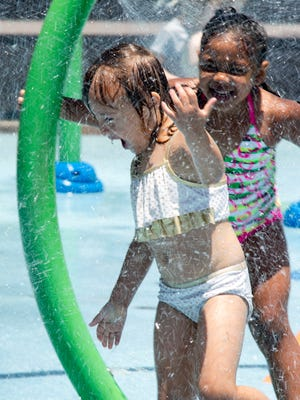 Marleigh Finnell (left) and Brooklynn Horne stay cool while playing at Pioneer Community Park's splash pad, 8755 N. 83rd Ave., Peoria.