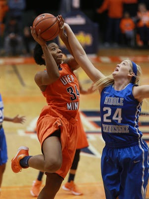 UTEP's Lawna Kennedy, left, puts up a shot against Middle Tennessee's Rebecca Reuter during the second quarter Thursday. See more photos at elpasotimes.com.