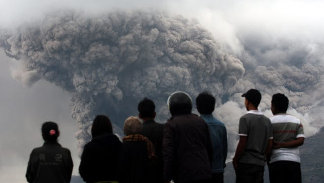 Villagers watch as Mount Sinabung releases pyroclastic flow during an eruption in North Sumatra, Indonesia, on Jan. 4.