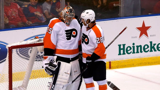 Philadelphia Flyers goalie Steve Mason (35) talks with center Claude Giroux (28)  after giving up four goals in the first period of a game against the Florida Panthers at BB&T Center.