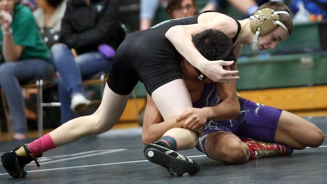 Dallin Stafford of Klahowya during a 2016 wrestling match. Stafford, now graduated, had hoped to serve as a volunteer assistant wrestling coach for the Eagles this year, before being told that school district policy barred most people ages 18 to 21 from volunteering. The district now plans to revise the policy to allow people like Stafford to volunteer.