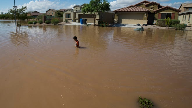 Water floods the streets in a neighborhood in Tolleson after a record-breaking monsoon storm passed through the Valley on Sept. 8, 2014.