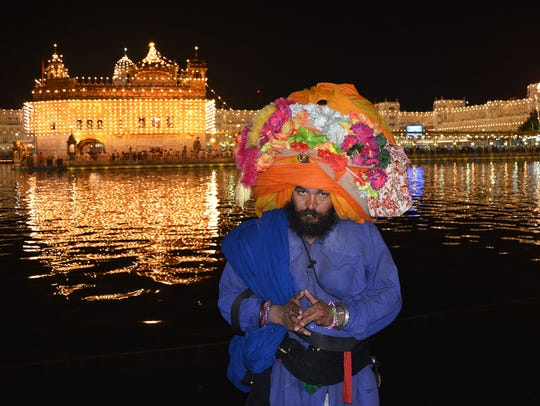A Sikh warrior pays respects in front of the illuminated